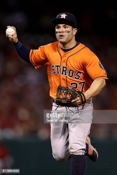 Jose Altuve of the Houston Astros looks to throw to first base in a rundown with JiMan Choi of the Los Angeles Angels of Anaheim during a game at...