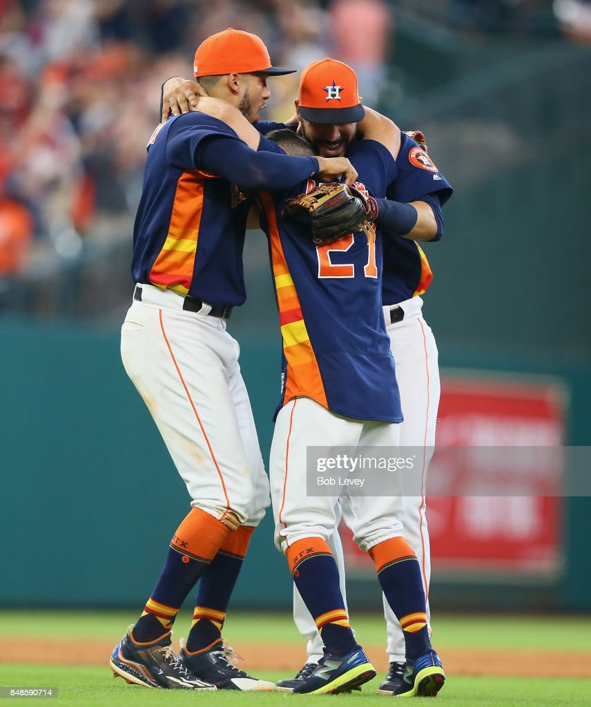 Jose Altuve #27 of the Houston Astros, Marwin Gonzalez #9 and Carlos Correa #1 celebrate after defeating the Seattle Mariners 7-1 to win the American League West division at Minute Maid Park on September 17, 2017 in Houston, Texas.