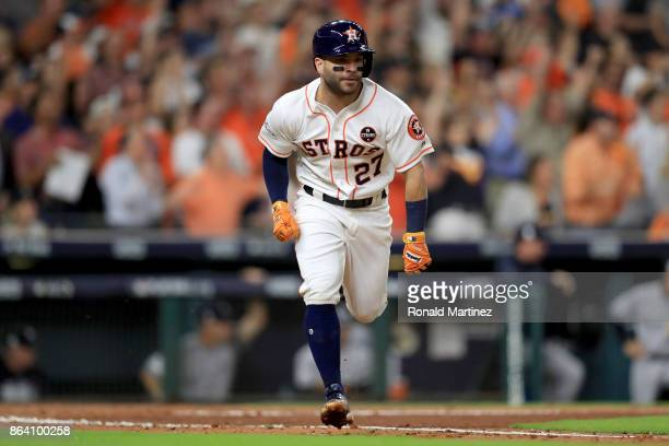 Jose Altuve of the Houston Astros reacts after hitting a single to left field to score Evan Gattis and Brian McCann against Luis Severino of the New...