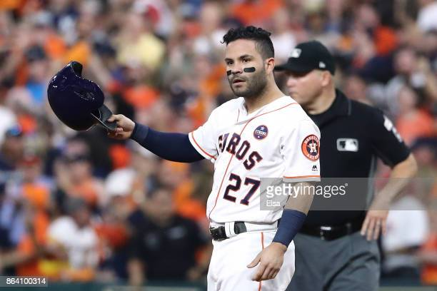 Jose Altuve of the Houston Astros reacts from first base after hitting a single to left field to score Evan Gattis and Brian McCann against Luis...