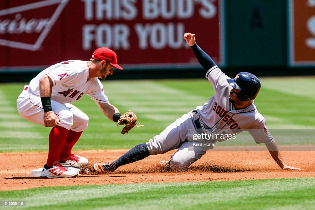 Jose Altuve #27 of the Houston Astros safely slides into 2nd base during the 1st inning beating the tag by Johnny Giavotella #12 of the Los Angeles Angels at Angel Stadium of Anaheim on June 29, 2016 in Anaheim, California.