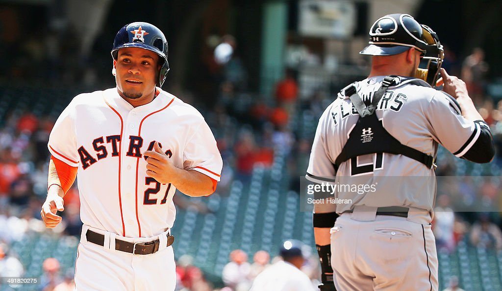 Jose Altuve #27 of the Houston Astros scores a run in the first inning as Tyler Flowers #21 of the Chicago White Sox looks on during their game at Minute Maid Park on May 17, 2014 in Houston, Texas.