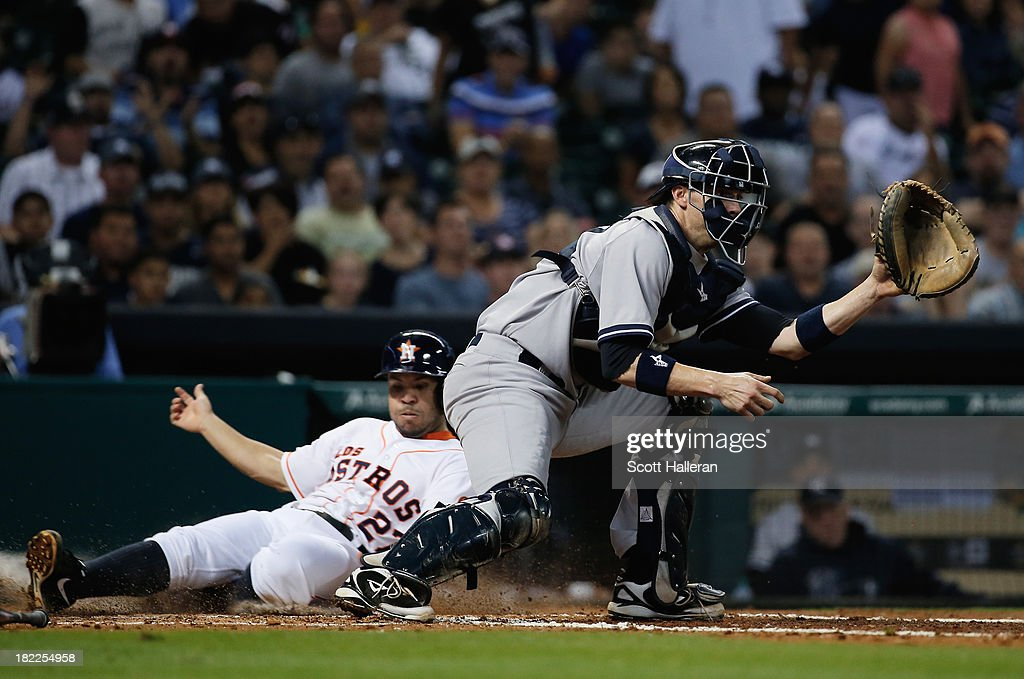 Jose Altuve #27 of the Houston Astros scores a run in the fourth inning as catcher Chris Stewart #19 waits for the ball at Minute Maid Park on September 28, 2013 in Houston, Texas.