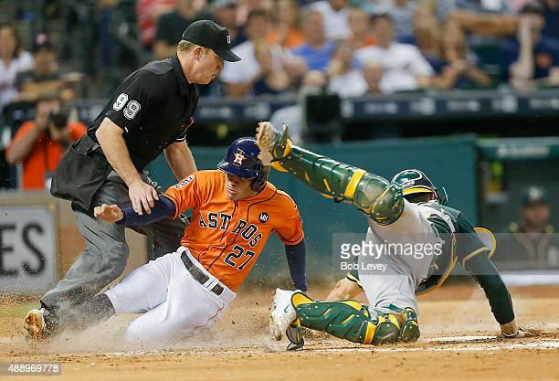 Jose Altuve of the Houston Astros scores as he slides past Carson Blair of the Oakland Athletics as home plate umpire Toby Basner makes the call in...