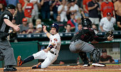 Jose Altuve of the Houston Astros scores in the fifth inning as slides around the tag attempt by Chris Herrmann of the Arizona Diamondbacks at Minute...