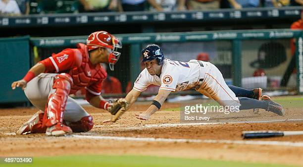 Jose Altuve of the Houston Astros scores in the seventh inning as Carlos Perez of the Los Angeles Angels of Anaheim is late on the tag at Minute Maid...