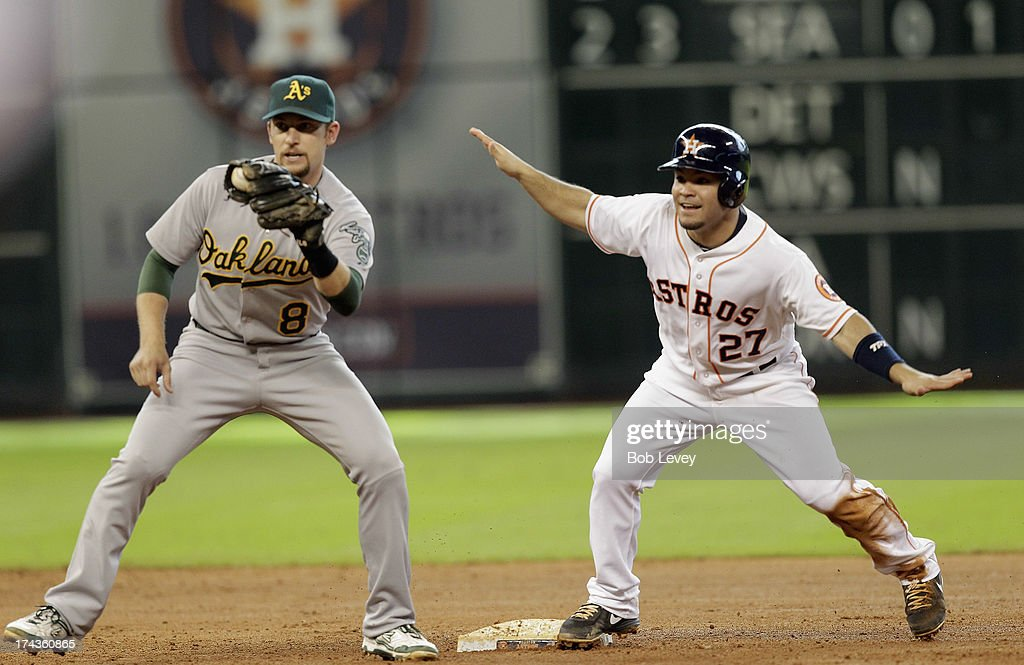 Jose Altuve #27 of the Houston Astros signals safe as shortstop Jed Lowrie #8 looks for the call from second base umpire at Minute Maid Park on July 24, 2013 in Houston, Texas.