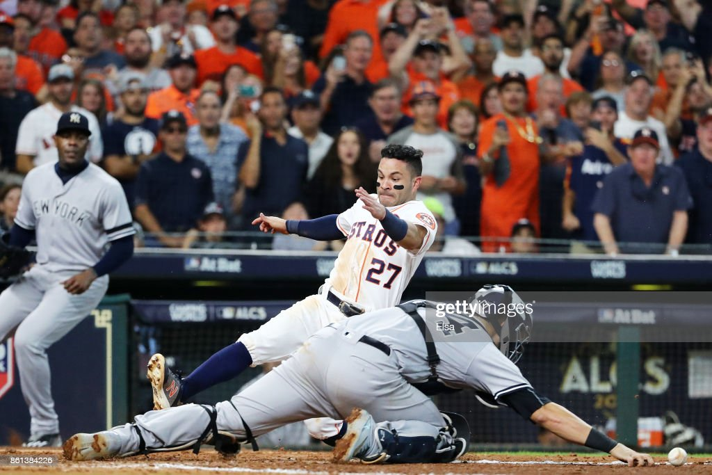 Jose Altuve #27 of the Houston Astros slides home to score the winning run against Gary Sanchez #24 of the New York Yankees in the ninth inning during game two of the American League Championship Series at Minute Maid Park on October 14, 2017 in Houston, Texas. The Astros defeated the Yankees 2 to 1.