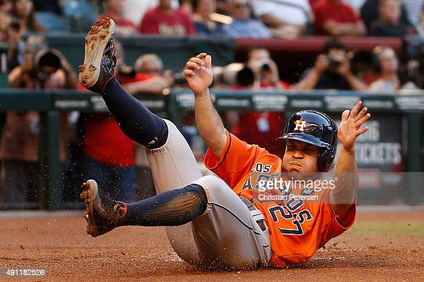 Jose Altuve of the Houston Astros slides in to score a first inning run against the Arizona Diamondbacks during the MLB game at Chase Field on...