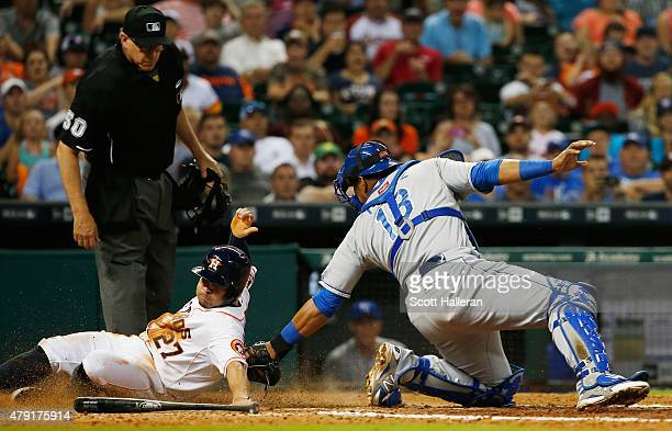 Jose Altuve of the Houston Astros slides into home plate under the tag of Salvador Perez of the Kansas City Royals in the seventh inning during their...