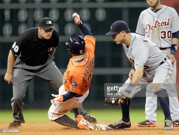 Jose Altuve of the Houston Astros slides safely in to second base as Ian Kinsler of the Detroit Tigers is late on the tag as umpire Mark Ripperger...