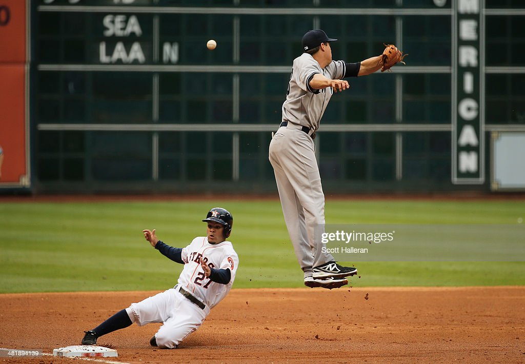 Jose Altuve #27 of the Houston Astros slides safely into third base in the first inning as Kelly Johnson #33 of the New York Yankees leaps for the ball during the game at Minute Maid Park on April 1, 2014 in Houston, Texas.
