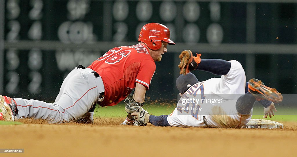Jose Altuve #27 of the Houston Astros tags out Kole Calhoun #56 of the Los Angeles Angels of Anaheim in the sixth inning as umpire Brian O'Nora makes the call at Minute Maid Park on September 2, 2014 in Houston, Texas.
