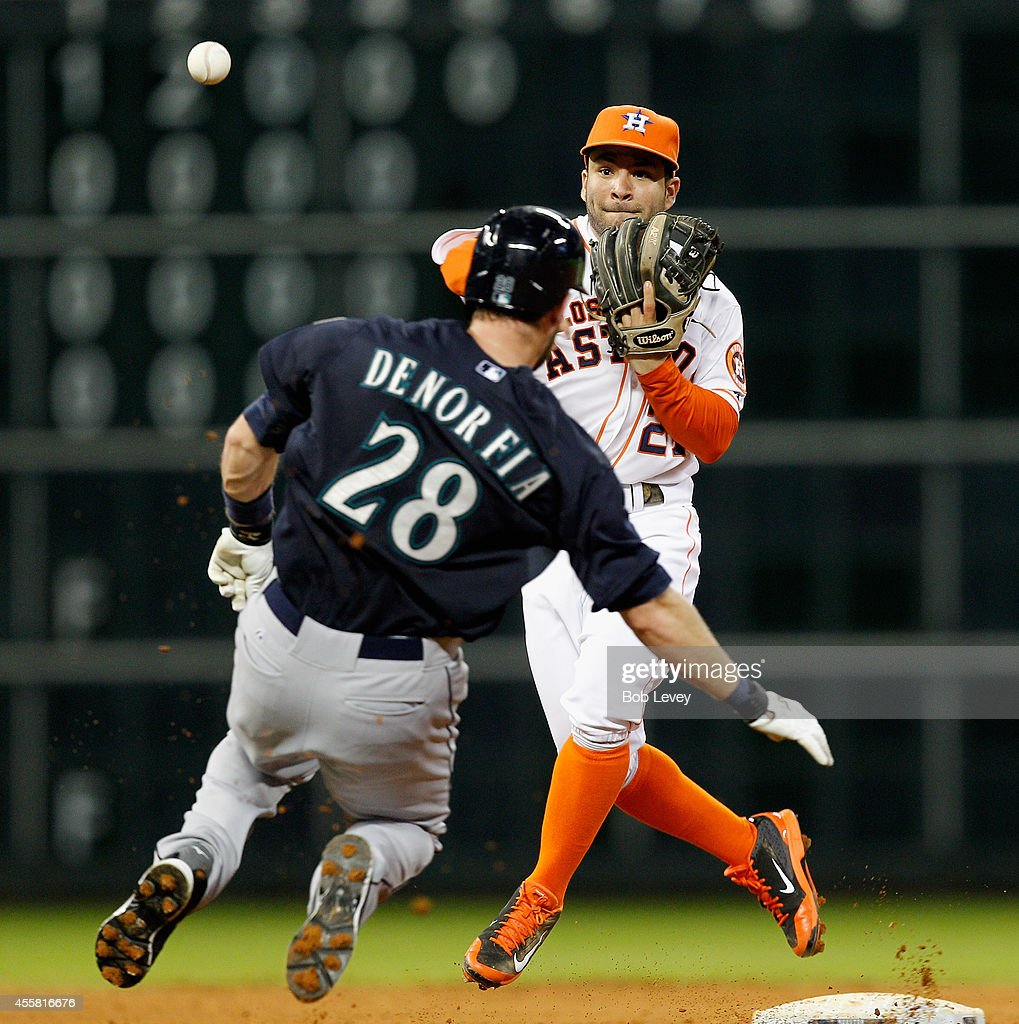 Jose Altuve #27 of the Houston Astros throws over Chris Denorfia #28 of the Seattle Mariners to complete a double play in the fifth inning at Minute Maid Park on September 20, 2014 in Houston, Texas.