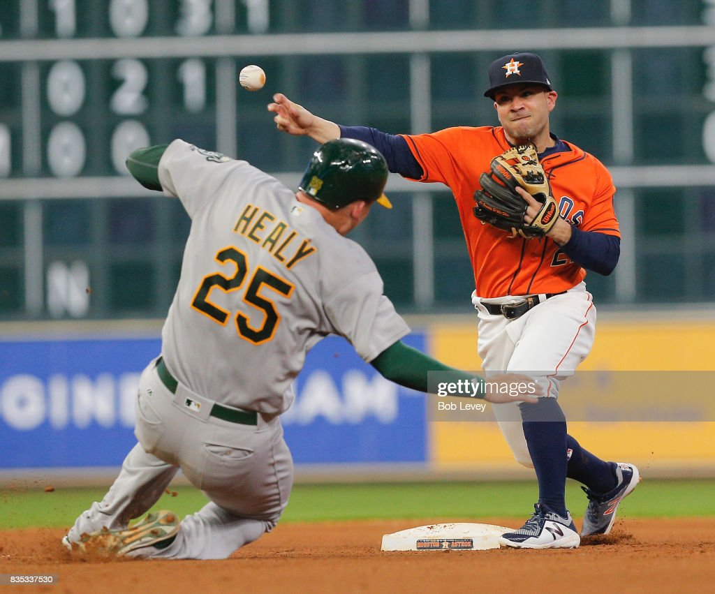 Jose Altuve #27 of the Houston Astros throws over Ryon Healy #25 of the Oakland Athletics to complete a double play in the seventh inning at Minute Maid Park on August 18, 2017 in Houston, Texas.