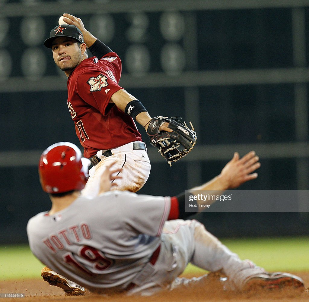 Jose Altuve of the Houston Astros throws to first base to complete a double play as Joey Votto of the Cincinnati Reds slides into second base on June...