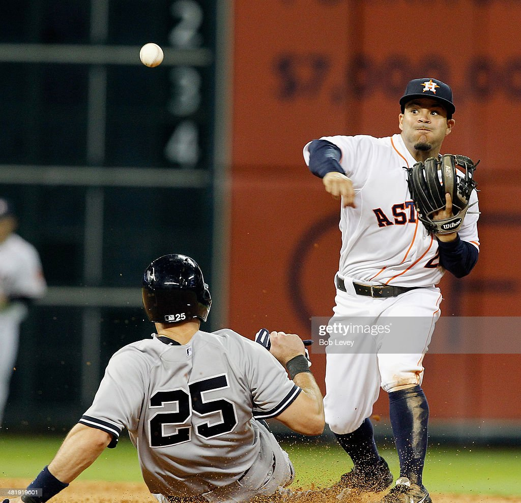 Jose Altuve #27 of the Houston Astros throws to first base to complete a double play as Mark Teixeira #25 of the New York Yankees slides into second base at Minute Maid Park on April 1, 2014 in Houston, Texas.
