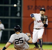 Jose Altuve of the Houston Astros throws to first base to complete a double play as Mark Teixeira of the New York Yankees slides into second base at...