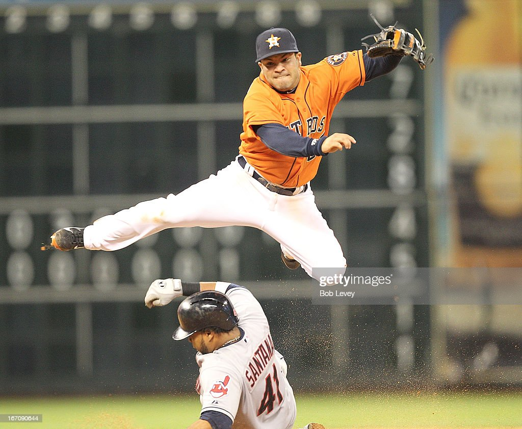 <a gi-track='captionPersonalityLinkClicked' href=/galleries/search?phrase=Jose+Altuve&family=editorial&specificpeople=7934195 ng-click='$event.stopPropagation()'>Jose Altuve</a> #27 of the Houston Astros turns a double play in the eighth inning as Carlos Santana #4 of the Cleveland Indians attempts to break up the play at Minute Maid Park on April 19, 2013 in Houston, Texas.