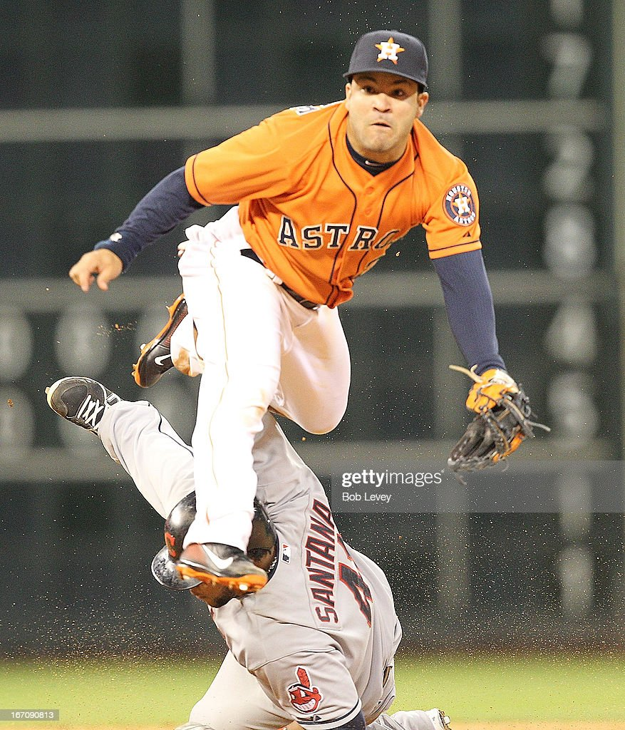 Jose Altuve #27 of the Houston Astros turns a double play in the eighth inning as Carlos Santana #4 of the Cleveland Indians attempts to break up the play at Minute Maid Park on April 19, 2013 in Houston, Texas.
