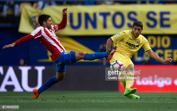 Jose Angel of Villarreal competes for the ball with Carlos Carmona of Real Sporting de Gijon during the La Liga match between Villarreal CF and Real...