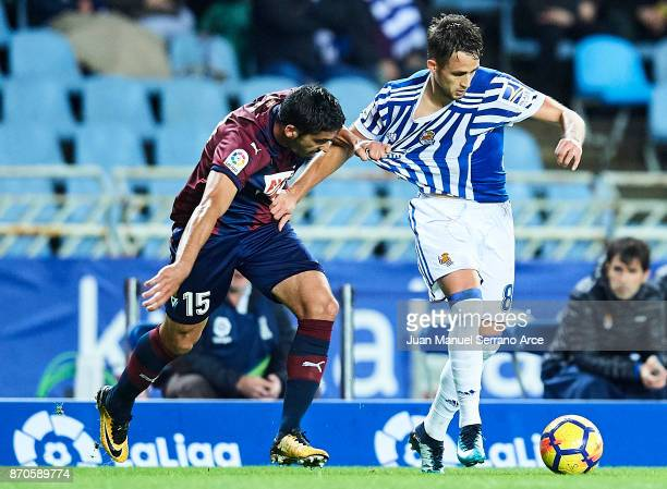 Jose Angel Valdes 'Cote' of SD Eibar competes for the ball with Adnan Januzaj of Real Sociedad during the La Liga match between Real Sociedad and...