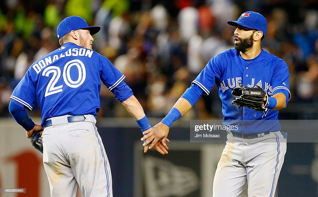Jose Bautista #19 and <a gi-track='captionPersonalityLinkClicked' href=/galleries/search?phrase=Josh+Donaldson&family=editorial&specificpeople=4959442 ng-click='$event.stopPropagation()'>Josh Donaldson</a> #20 of the Toronto Blue Jays celebrate after defeating the New York Yankees at Yankee Stadium on August 7, 2015 in the Bronx borough of New York City. Both players hit home runs in their teams 2-1 victory.