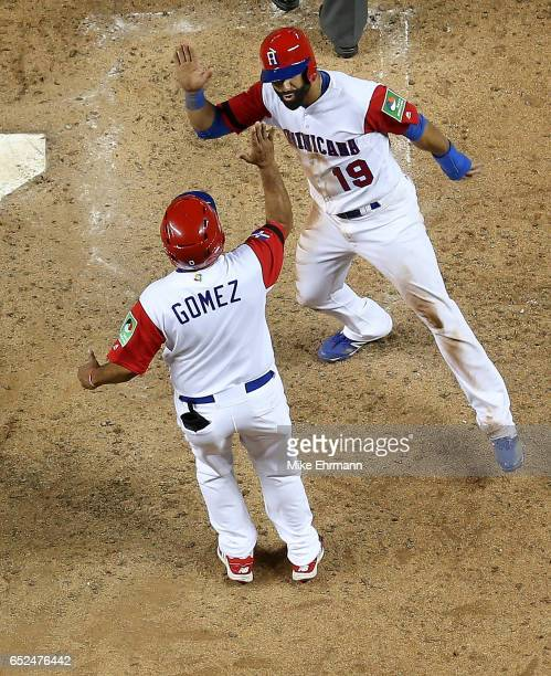 Jose Bautista of the Dominican Republic is congratulated after scoring on a three run home run by Nelson Cruz during the eighth inning during a Pool...