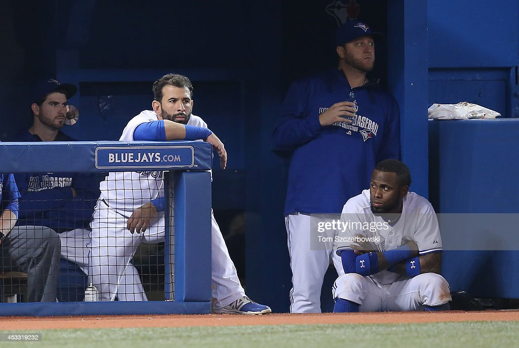 Jose Bautista #19 of the Toronto Blue Jays and Jose Reyes #7 look on from the top step of the dugout during MLB game action against the Baltimore Orioles on August 7, 2014 at Rogers Centre in Toronto, Ontario, Canada.