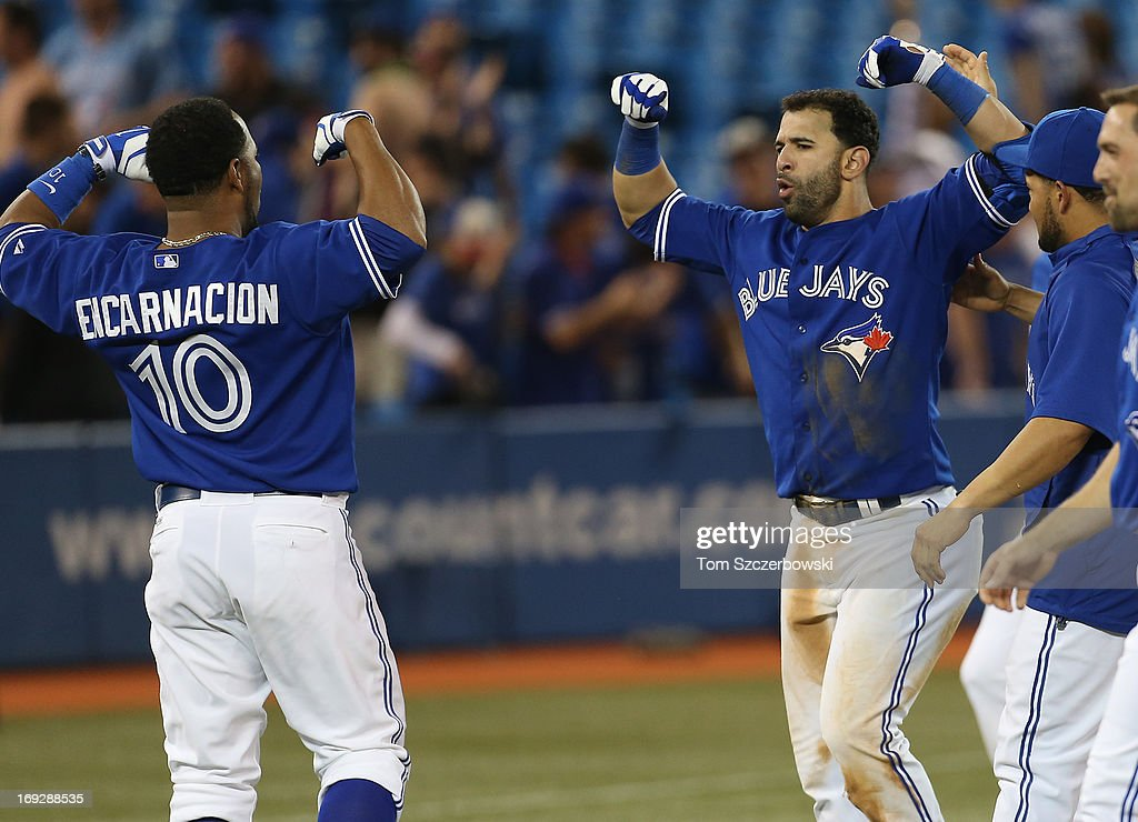 Jose Bautista #19 of the Toronto Blue Jays celebrates his game-winning hit in the tenth inning with Edwin Encarnacion #10 during MLB game action against the Tampa Bay Rays on May 22, 2013 at Rogers Centre in Toronto, Ontario, Canada.