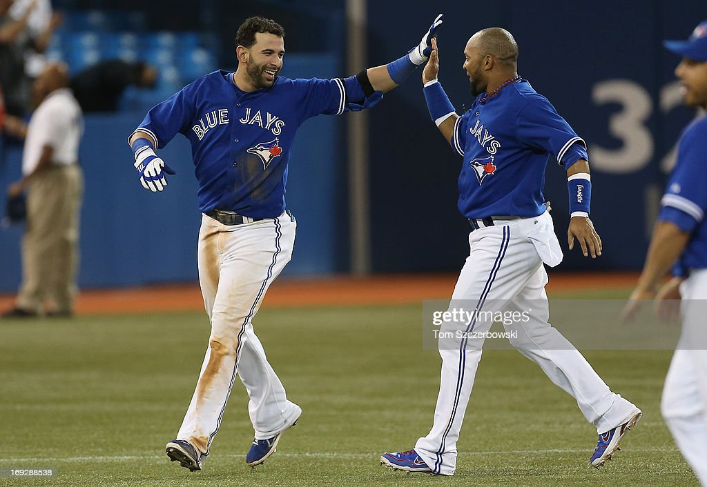 Jose Bautista #19 of the Toronto Blue Jays celebrates his game-winning hit in the tenth inning with Emilio Bonifacio #1 during MLB game action against the Tampa Bay Rays on May 22, 2013 at Rogers Centre in Toronto, Ontario, Canada.