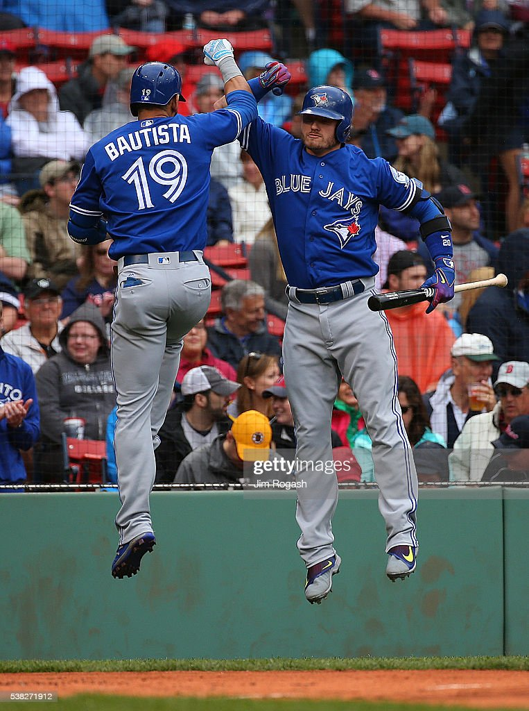 Jose Bautista of the Toronto Blue Jays celebrates his home run with Josh Donaldson against the Boston Red Sox in the first inning at Fenway Park on...