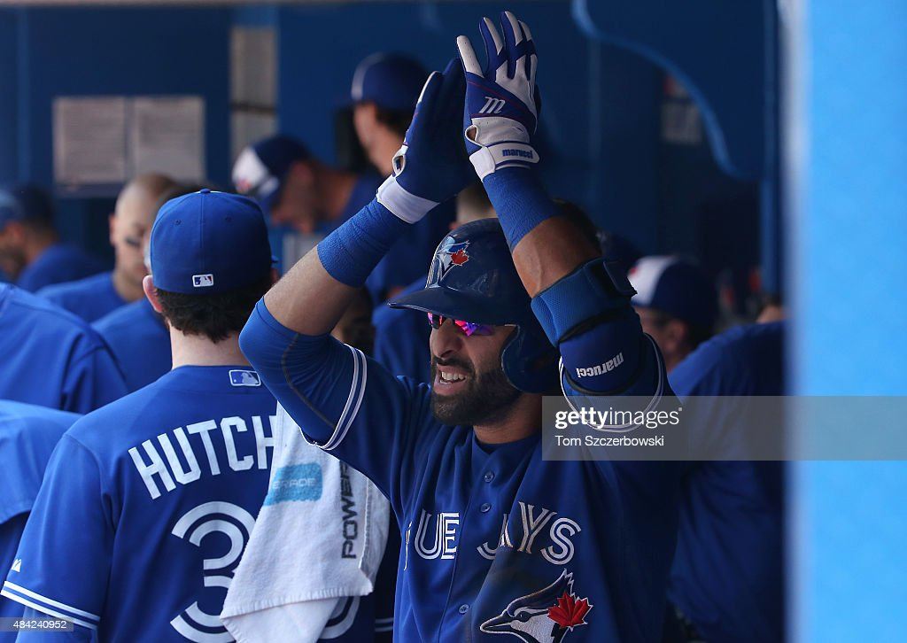 Jose Bautista #19 of the Toronto Blue Jays celebrates his two-run home run after being congratulated by Drew Hutchison #36 in the third inning during MLB game action against the New York Yankees on August 16, 2015 at Rogers Centre in Toronto, Ontario, Canada.