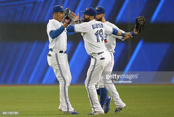 Jose Bautista of the Toronto Blue Jays celebrates their victory with Ezequiel Carrera and Kevin Pillar during MLB game action against the Tampa Bay...