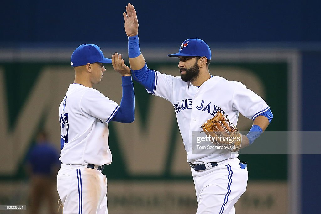 Jose Bautista #19 of the Toronto Blue Jays celebrates their victory with Ryan Goins #17 during MLB game action against the Houston Astros on April 9, 2014 at Rogers Centre in Toronto, Ontario, Canada.