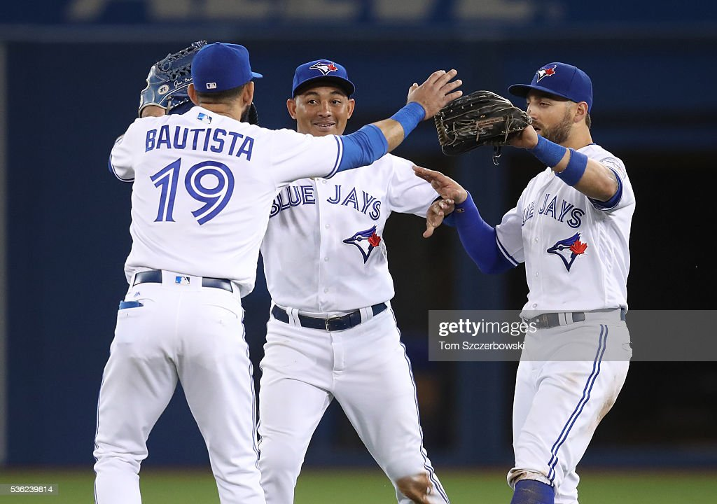 Jose Bautista of the Toronto Blue Jays celebrates their victory with Kevin Pillar and Ezequiel Carrera during MLB game action against the New York...