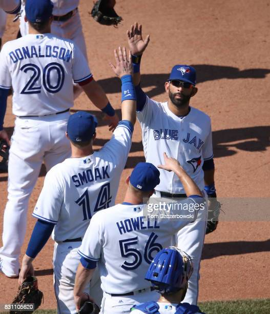Jose Bautista of the Toronto Blue Jays celebrates their victory with Justin Smoak during MLB game action against the Pittsburgh Pirates at Rogers...