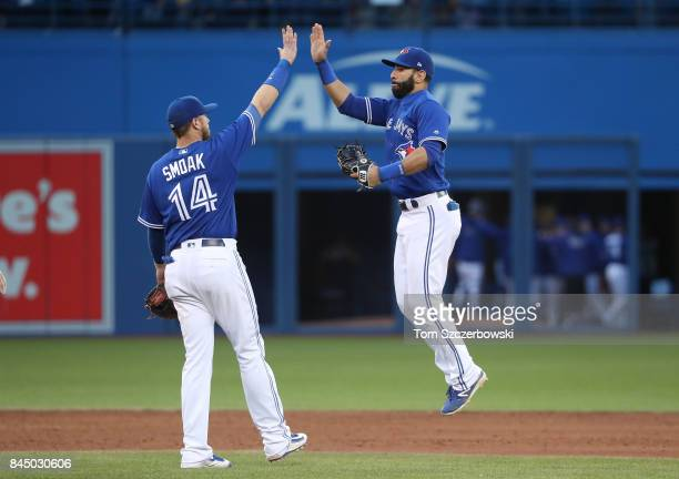 Jose Bautista of the Toronto Blue Jays celebrates their victory with Justin Smoak during MLB game action against the Detroit Tigers at Rogers Centre...