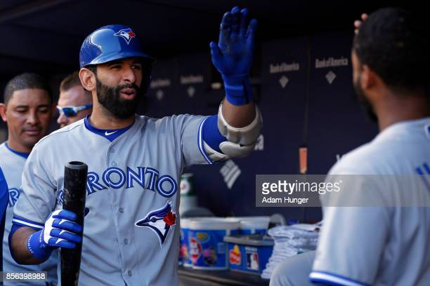 Jose Bautista of the Toronto Blue Jays celebrates with Richard Urena of the Blue Jays after hitting a sacrifice fly against the New York Yankees...