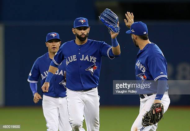 Jose Bautista of the Toronto Blue Jays celebrates with teammates after making a diving catch to end the seventh inning against the Texas Rangers...