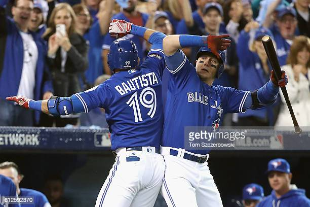 Jose Bautista of the Toronto Blue Jays celebrates with Troy Tulowitzki after hitting a solo home run in the second inning against the Baltimore...