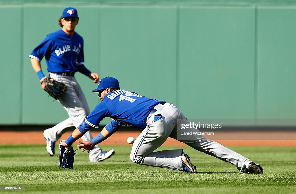 Jose Bautista #19 of the Toronto Blue Jays dives but misses a fly ball in left field against the Boston Red Sox during the game on May 12, 2013 at Fenway Park in Boston, Massachusetts.