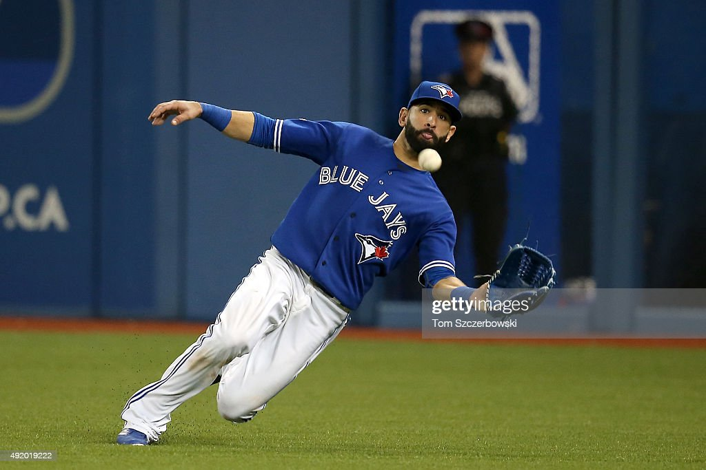 Jose Bautista #19 of the Toronto Blue Jays dives to make a catch and end the seventh inning against the Texas Rangers during game two of the American League Division Series at Rogers Centre on October 9, 2015 in Toronto, Canada.