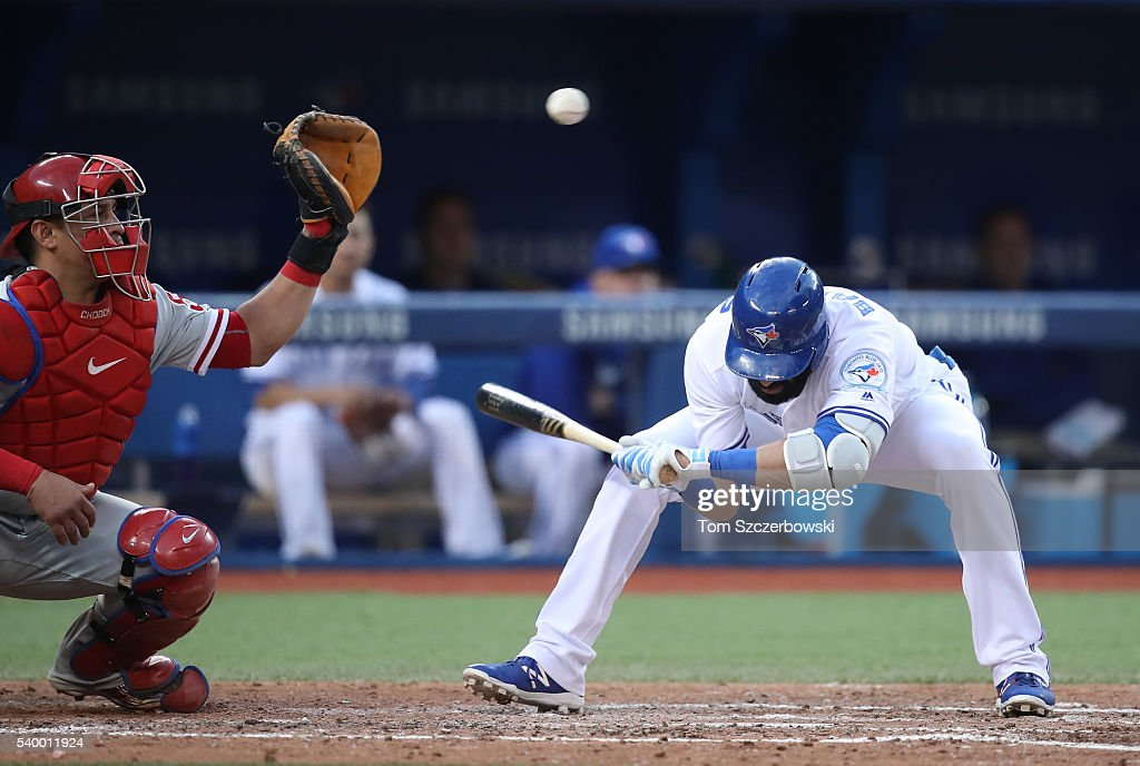 Jose Bautista of the Toronto Blue Jays ducks under a high pitch in the fifth inning during MLB game action as Carlos Ruiz of the Philadelphia...