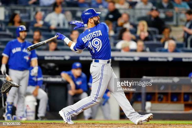 Jose Bautista of the Toronto Blue Jays follows through on a seventh inning two run home run against the New York Yankees at Yankee Stadium on May 1...