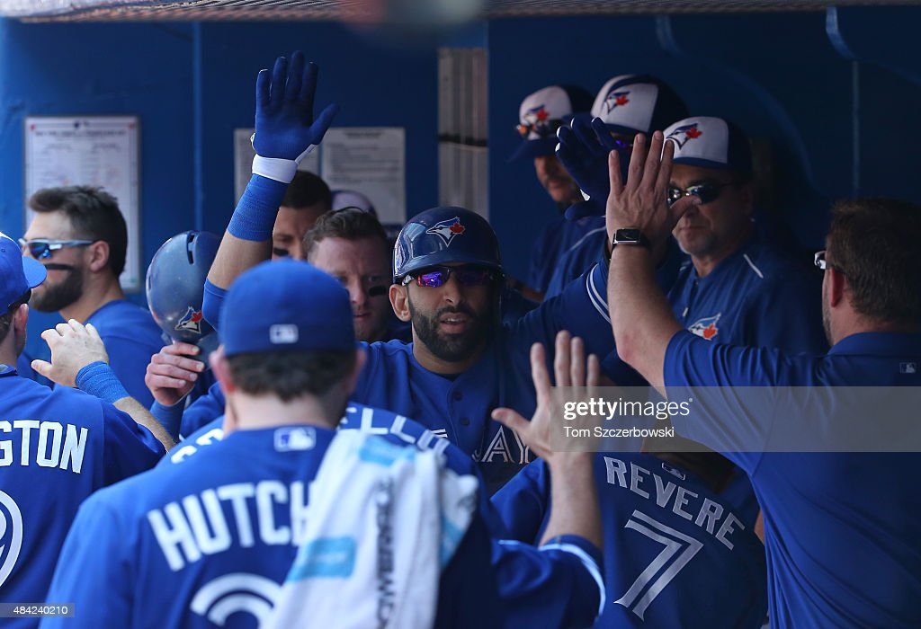 Jose Bautista #19 of the Toronto Blue Jays is congratulated by Drew Hutchison #36 and teammates in the dugout after hitting a two-run home run in the third inning during MLB game action against the New York Yankees on August 16, 2015 at Rogers Centre in Toronto, Ontario, Canada.