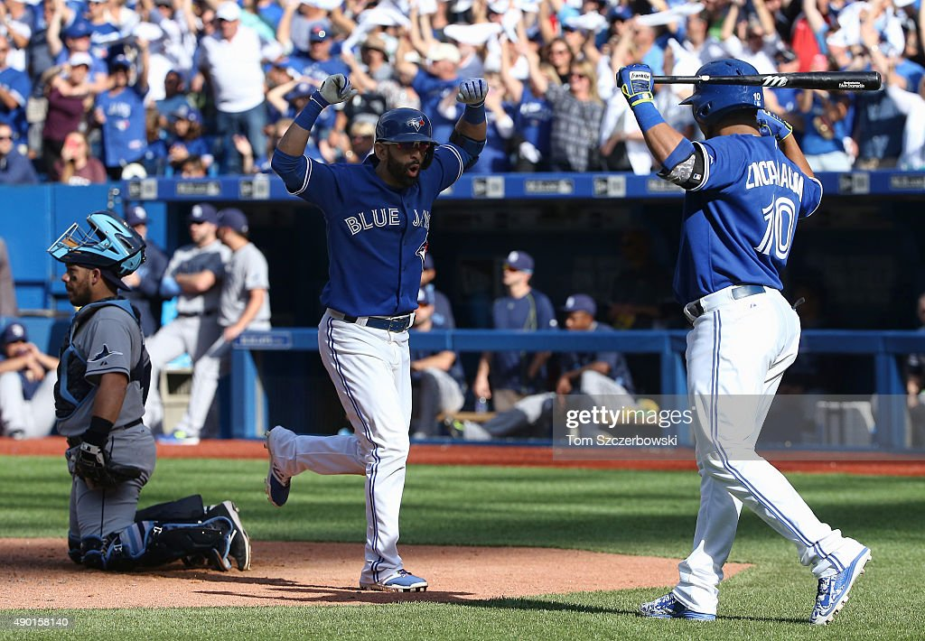 Jose Bautista #19 of the Toronto Blue Jays is congratulated by Edwin Encarnacion #10 after hitting a solo home run in the eighth inning during MLB game action against the Tampa Bay Rays on September 26, 2015 at Rogers Centre in Toronto, Ontario, Canada.