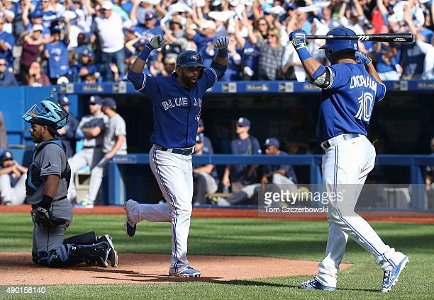 Jose Bautista of the Toronto Blue Jays is congratulated by Edwin Encarnacion after hitting a solo home run in the eighth inning during MLB game...