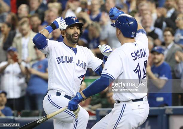 Jose Bautista of the Toronto Blue Jays is congratulated by Justin Smoak after hitting a solo home run in the fourth inning during MLB game action...