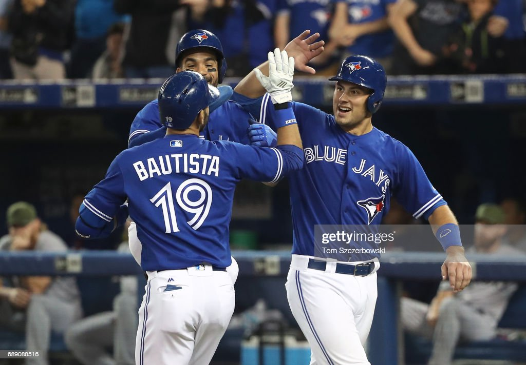 Jose Bautista #19 of the Toronto Blue Jays is congratulated by Luke Maile #22 and Devon Travis #29 after hitting a three-run home run in the fifth inning during MLB game action against the Texas Rangers at Rogers Centre on May 27, 2017 in Toronto, Canada.
